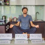 "Man sitting cross legged while meditating behind three cards that say ""fasting"""